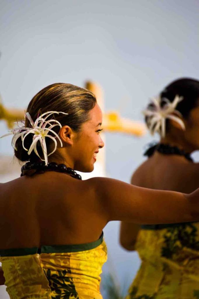 Image of a woman wearing a yellow Hawaiian dress and a big white flower in her hair.