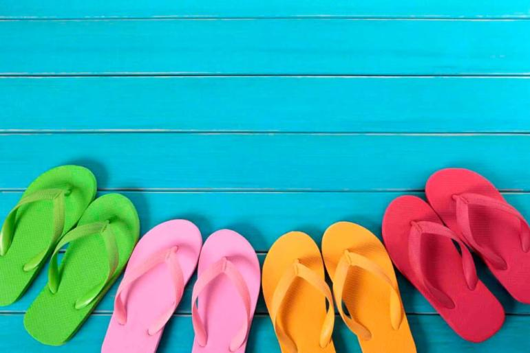 One of the coolest Hawaii culture facts is that people always remove their shoes before going in a house. Image of 4 pairs of flip flops on a blue deck.
