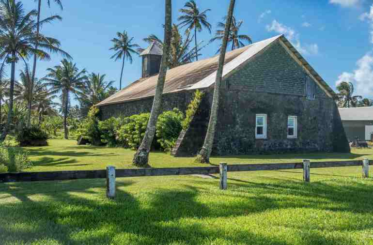 Another fun Road to Hana stop is the Keanae Point church on Maui. Image of a stone church surrounded by palm trees.