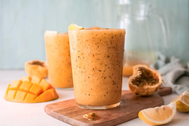 Learn how to make this mango passion fruit wine slushie by top Hawaii blog Hawaii Travel with Kids. Image of two glasses with tropical wine slushies surrounded by Hawaiian fruit.