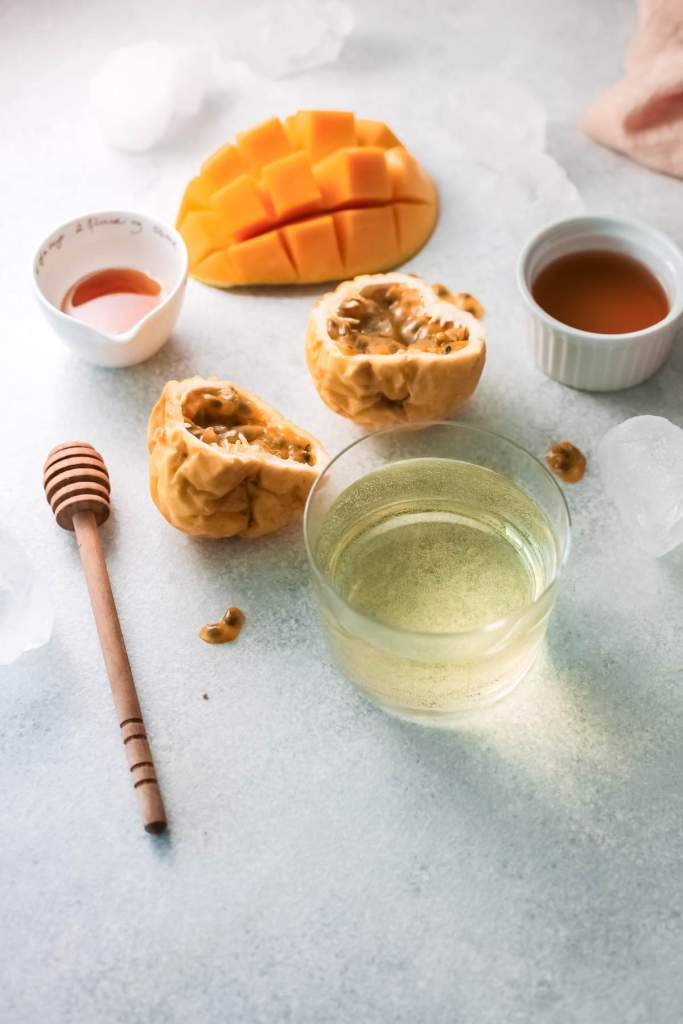 Ingredients you'll need to make this mango wine recipe. Image of mango, passion fruit, wine, and honey
