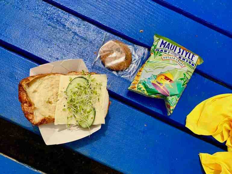 Image of a croissant sandwich, a cookie, and chips as part of the Kauai Tubing tour lunch.