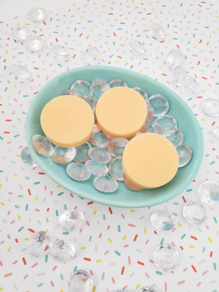 Find out how to make this DIY mango butter lotion recipe by top Hawaii blog Hawaii Travel with Kids. Image of 3 mango lotion bars in a blue dish.
