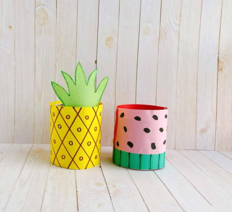 Find out how to make a paper pineapple craft by top Hawaii blog Hawaii Travel with Kids. Image of a toilet paper roll pineapple and watermelon craft.