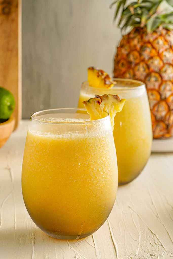Learn how to make mango pineapple mocktails by top Hawaii blog Hawaii Travel with Kids. Image of two glasses filled with Hawaiian drinks with a pineapple in the background.