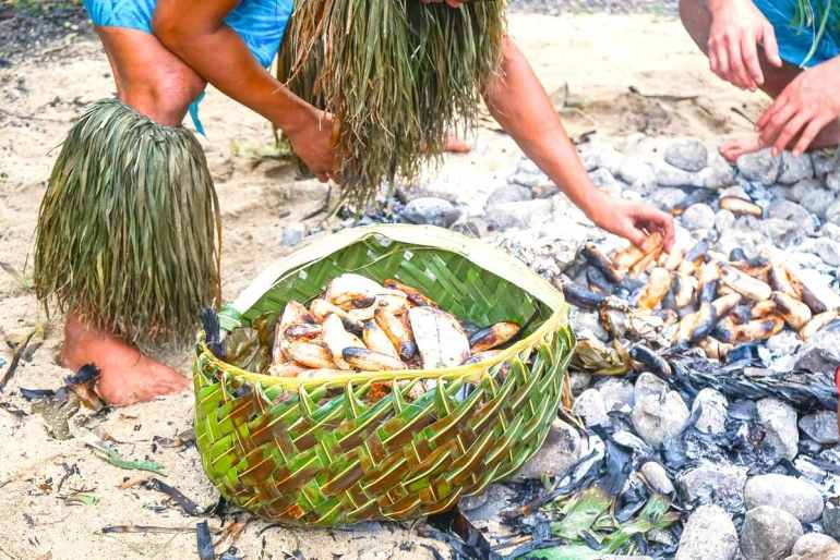 Most Hawaiian luaus on Oahu don't offer traditional Samoan food in addition to Hawaiian food. Image of a man preparing Samoan food on an Umu oven.
