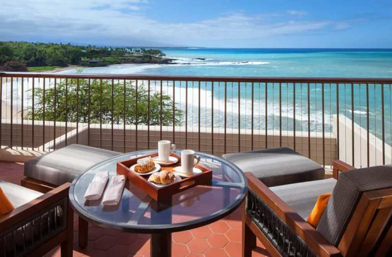 The Mauna Kea Beach Hotel is one of the best places to stay in Big Island Hawaii with kids. Image of the lanai overlooking the ocean.