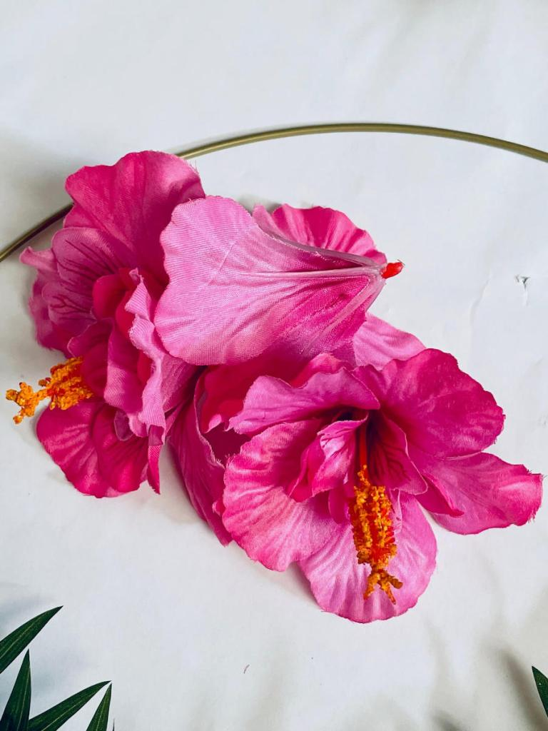 Image of three pink silk hibiscus blossoms on a white surface.
