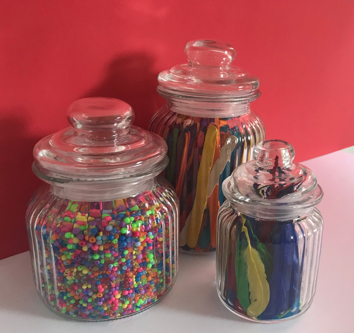 Glass jars with beads, lollipop sticks and feathers
