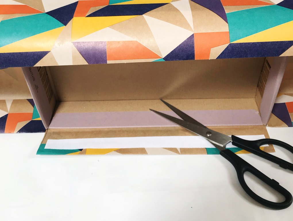 Clarks shoebox on its side with double-sided tap and scissors