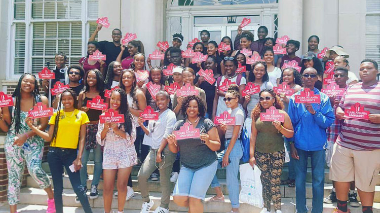 """HBCU College Tours students take a group photo with the Stepping In the Right Direction Tour director Nicole Ford. The group members are holding up red """"CAU"""" signs on the campus of Clark Atlanta University."""