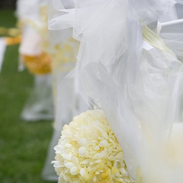 Yellow flowers and white ribbons aisle decorations