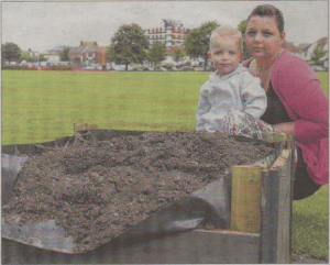 Sarah Jane Phillips and her three-year-old son Frankie Ray with some of the damage in the Memorial Park