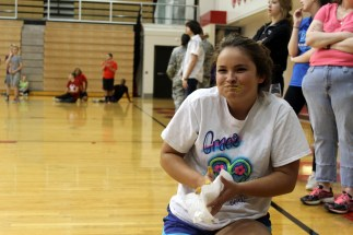 Junior Gracie Parrish finishes eating the mustard covered raisins during the food relay.