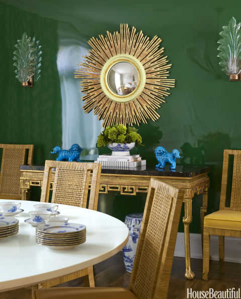 """""""From the very beginning, my client and I bonded over color,"""" says Weiss, who lacquered a luscious green paint, Benjamin Moore's Seaweed, on the dining room walls. Bielecky Brothers cane chairs, upholstered in Pierre Frey's Opera-Velours, surround a custom-made table. Vintage sconces from Lucca Antiques flank Julian Chichester's Hobbs sunburst mirror."""