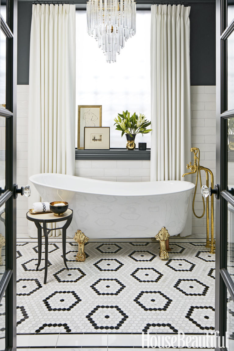 "Designed by SuzAnn Keltzein, the dark walls and geometric tiles in this ""dramatic"" washroom get an extra dose of luxury with a lavish chandelier. Bonus points for the asymmetrical claw-footed tub."