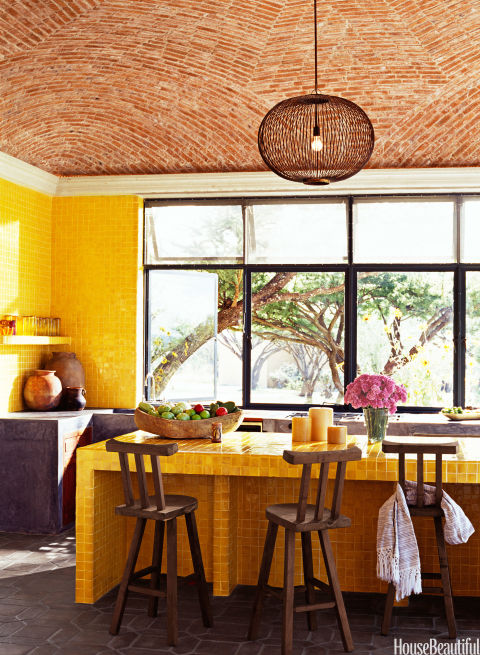 "Doing the kitchen in one color tile breaks with the Mexican tradition of ""having a riot of colors,"" designer John Houshmand says of his hacienda in Mexico. And doing it in yellow seems ""totally American. It's a pretty darn happy place to be."""