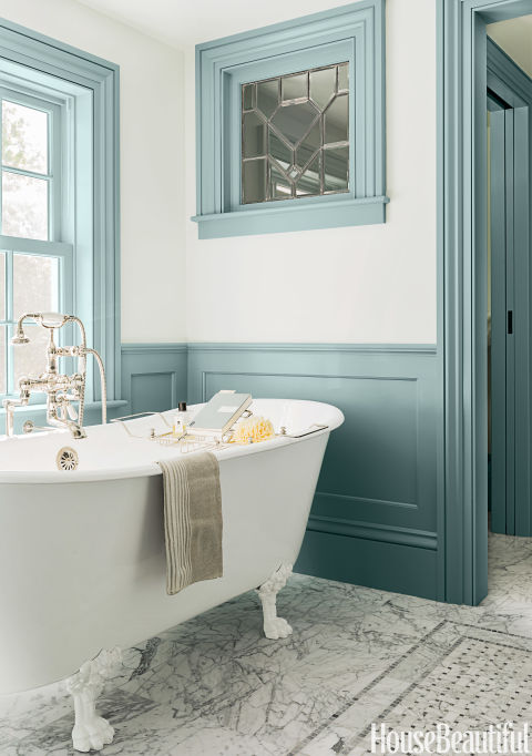 "Back in the 18th-century when this Massachusetts farmhouse was built, there was no such thing as a master bath. So architect Michael T. Gray and interior designer Hattie Holland, both of Carpenter & MacNeille, carved one out of a hallway and added wainscoting and window casings to create a sense of the past. Painted a deep blue-gray, they stand out against the pale blue walls. The color ""has a historic feeling with that gray cast and plays off the Carrara marble so well,"" Holland says. In the center of the floor, a virtual rug made of marble in a basket-weave pattern adds another layer of detail to the room. The cast-iron tub looks old but is actually new. ""It's a slipper tub, higher on each end, and that little swoop gives it a sense of elegance,"" Holland says. ""And the legs let you see the marble underneath, which makes a small space feel more open."" An antique leaded-glass window, found at a salvage yard, is set into the wall adjoining the water closet. It lets light into that room, making it feel less enclosed while still maintaining privacy. It's another old-world touch that creates instant character. ""The goal was to keep the farmhouse charm but make it more comfortable,"" Holland says. ""You can lean back against that great rollover on the tub's rim and soak for hours."" The Missy tub is paired with a floor-mounted tub filler in polished nickel, both by Sunrise Specialty. Carrara marble tile and basket-weave insert from Cumar. The walls are painted in Borrowed Light with trim in Parma Gray, both by Farrow & Ball."