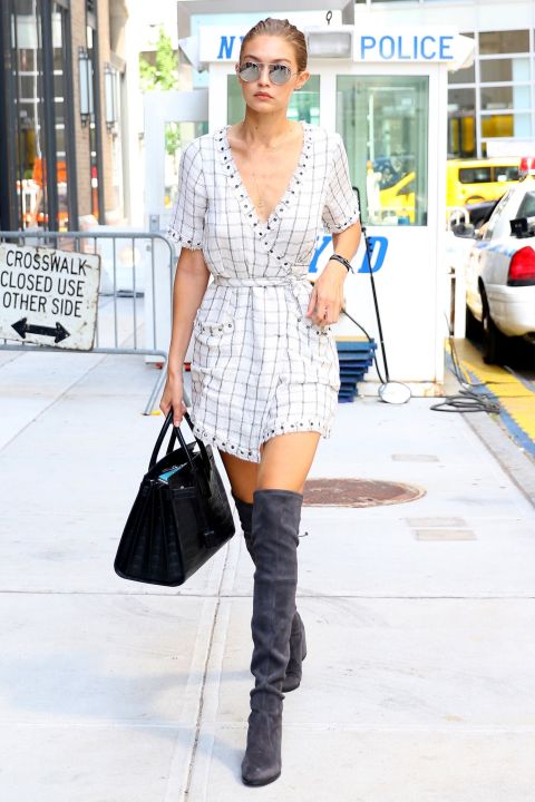 The model spent Labor Day in Manhattan wearing a windowpane-checked romper with gray over-the-knee boots from Stuart Weitzman and black crocodile leather bag by Saint Laurent.