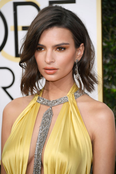 Rocking what looks like a new lob cut, Emily Ratajkowski's hair is actually expertly pinned and rolled into place—creating the appearance of a dramatic chop. Her monochromaticpeachy makeup (using all Chanel makeup) is gorgeous, too.