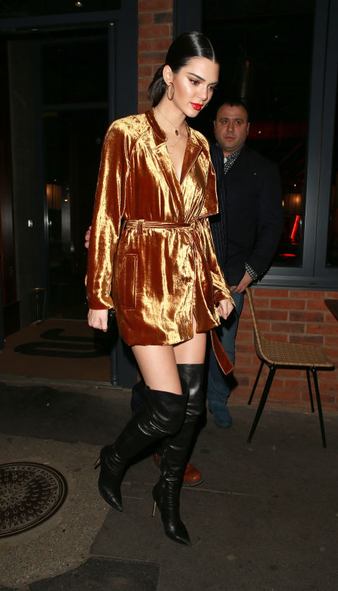 In a metallic gold velvet wrap dress, black leather over-the-knee boots, layered necklaces and gold hoop earrings after her LOVE Magazine signing in London.