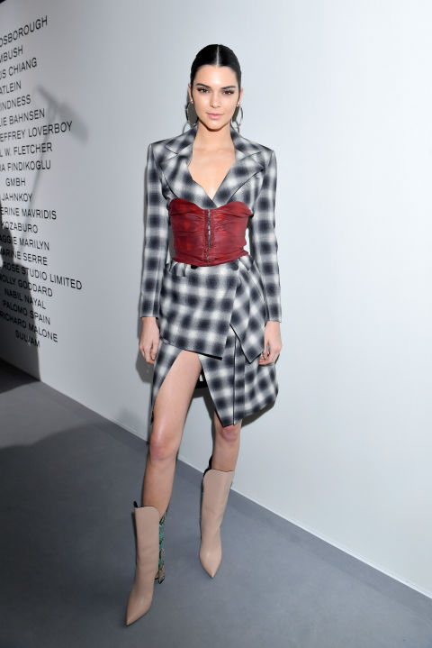 In a checked wrap dress wrapped with a red corset and beige leather pointed toe bootsat the LVMH Prize cocktail reception in Paris.