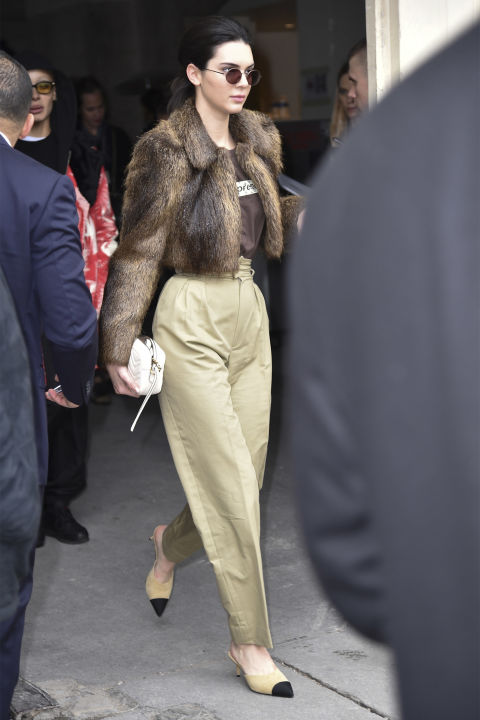 In a browncropped fur coat, Supreme x Louis Vuitton t-shirt and high-waisted khaki pants with Chanel pumps and Krewe sunglasses while leaving the Chanel show in Paris.