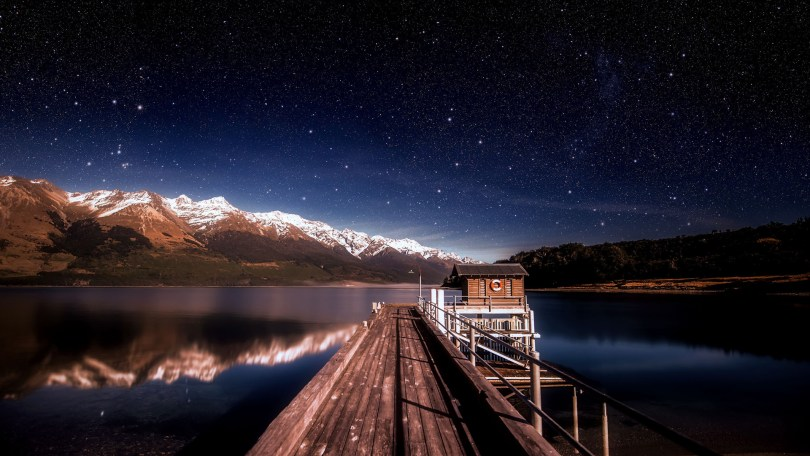 Landscape imgage of a house and pier on a lake with mountains in the background