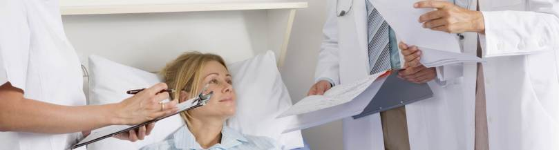 Woman in hospital bed talking to doctors