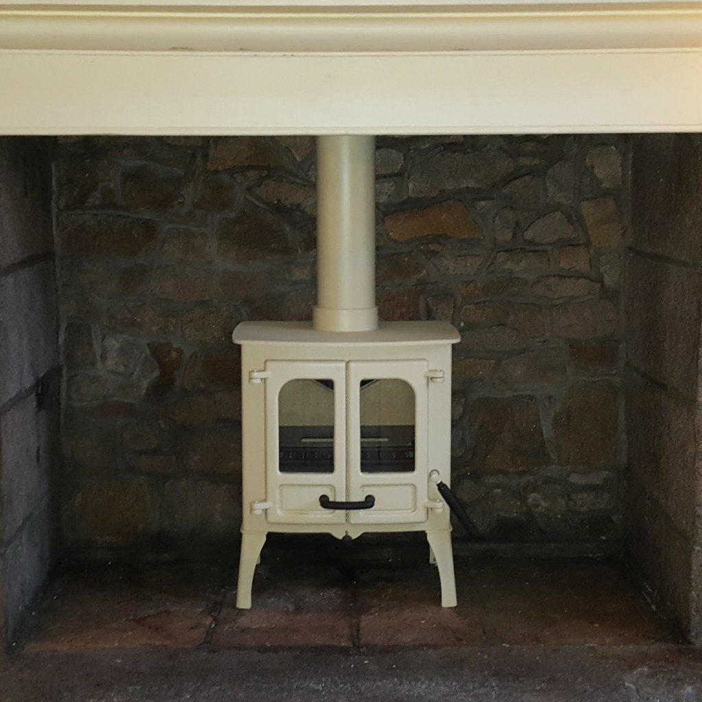Charnmood Island One with High legs and 6 inch flue, stainless steel liner in set in old granite fireplace