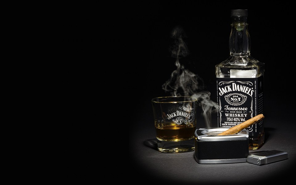 A bottle of Jack Daniels Tennessee whiskey next to a glass with a measure poured into it.