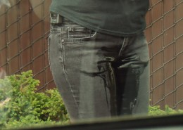 Close-up image of Alisha peeing in her jeans in public.