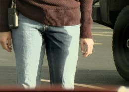 Close-up shot of Alisha peeing her pants in a parking lot.
