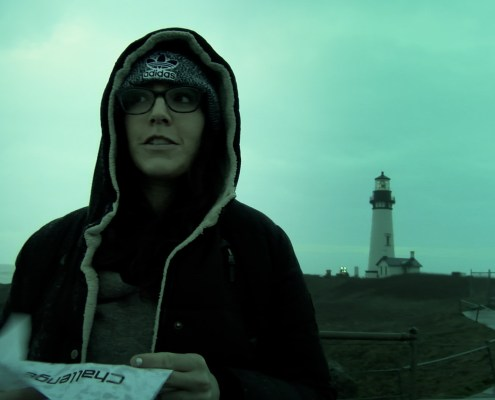Standing out in a storm in front of a creepy lighthouse, Alisha contemplates her most recent challenge.