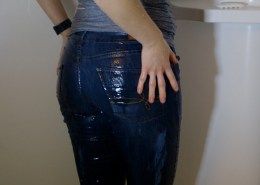 Alisha's jeans are soaking wet as she takes a shower fully clothed.