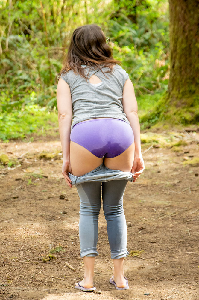 Rear view of Alisha removing her wet jeans outdoors.