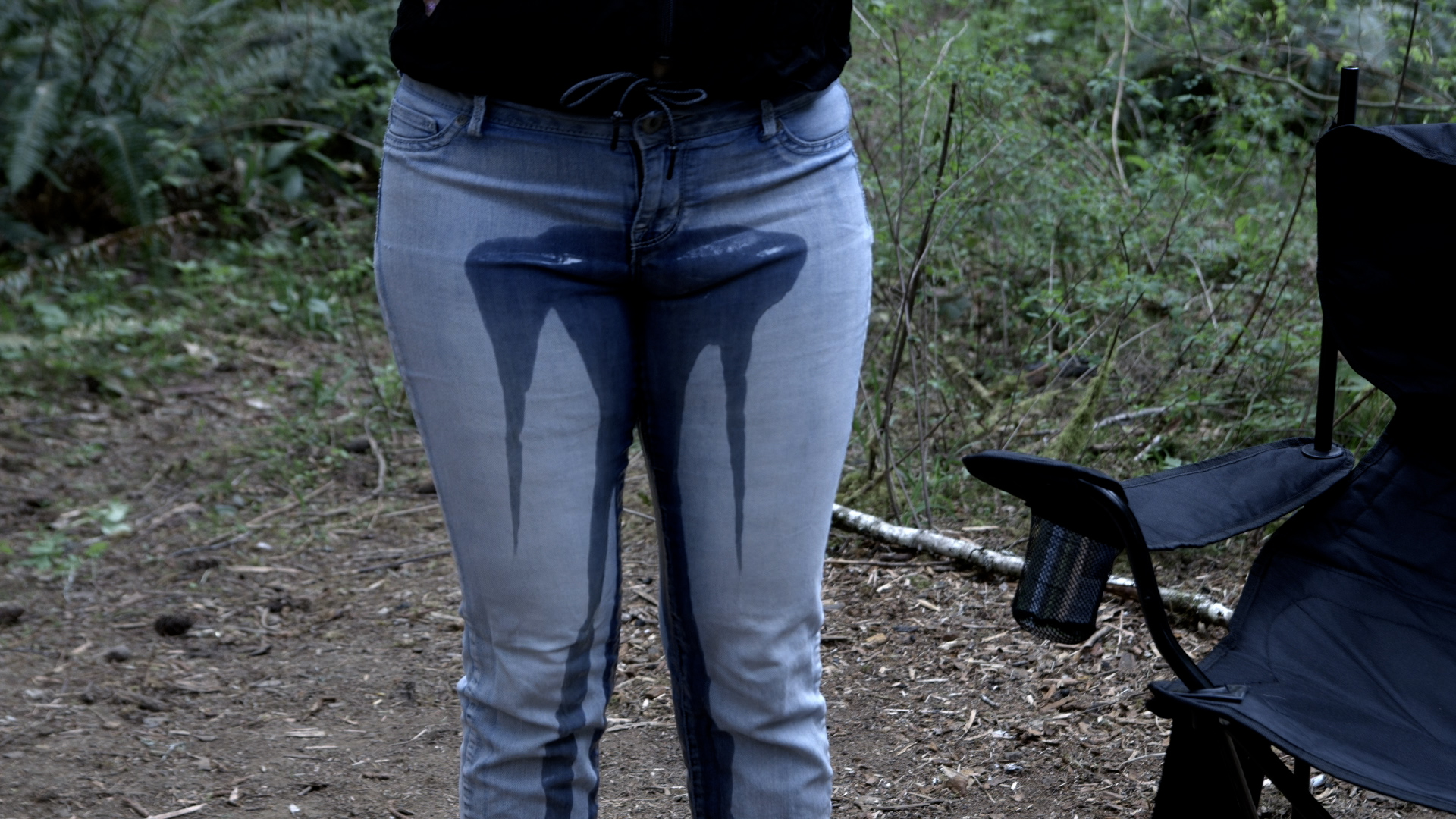 Close-up shot of Alisha peeing in her jeans while standing next to the campfire.