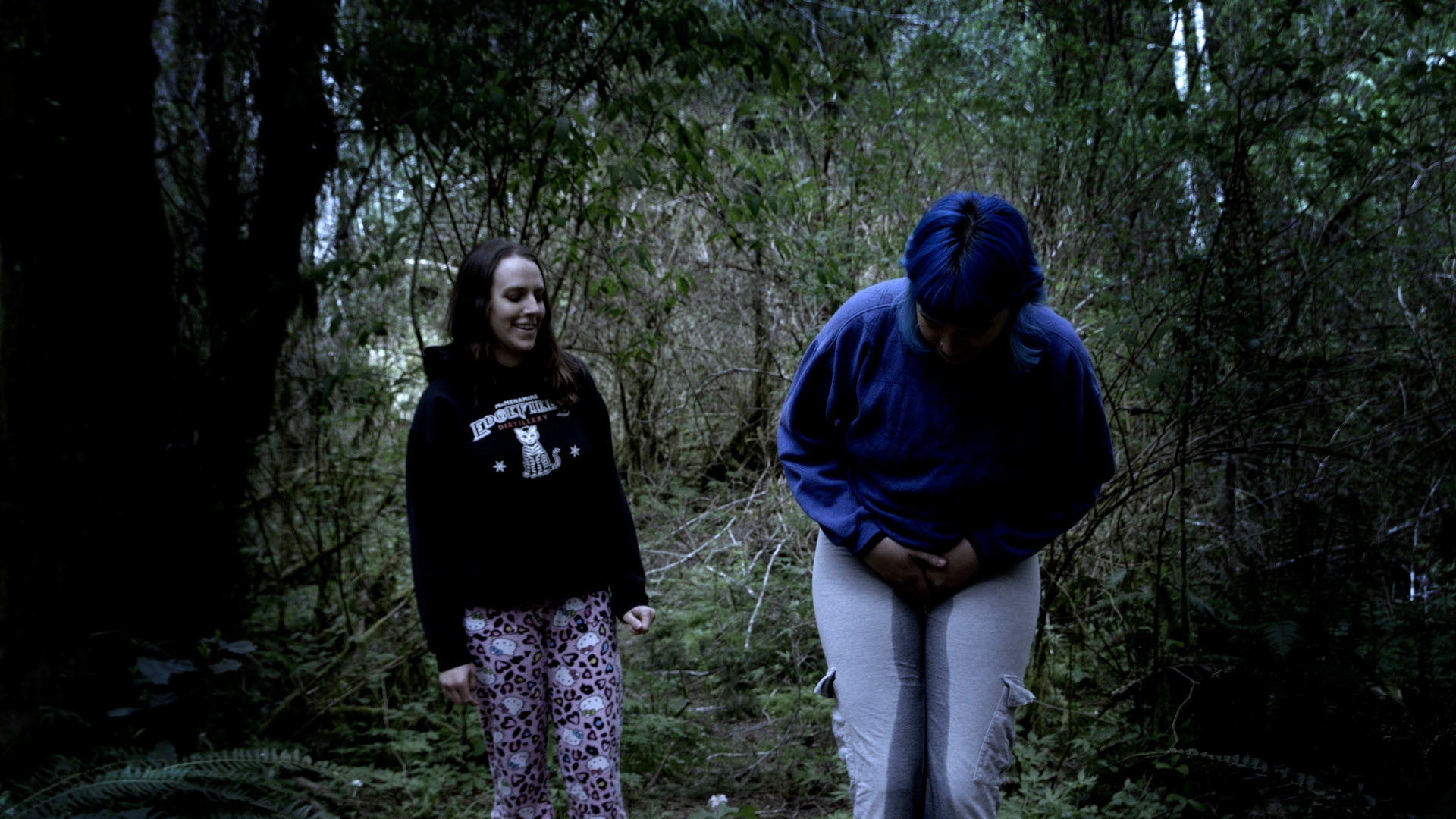 Medium shot of Olivia wetting her pants on accident as Alisha watches.