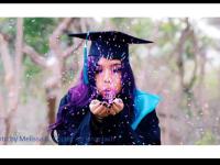 College graduate in gown blowing confetti.