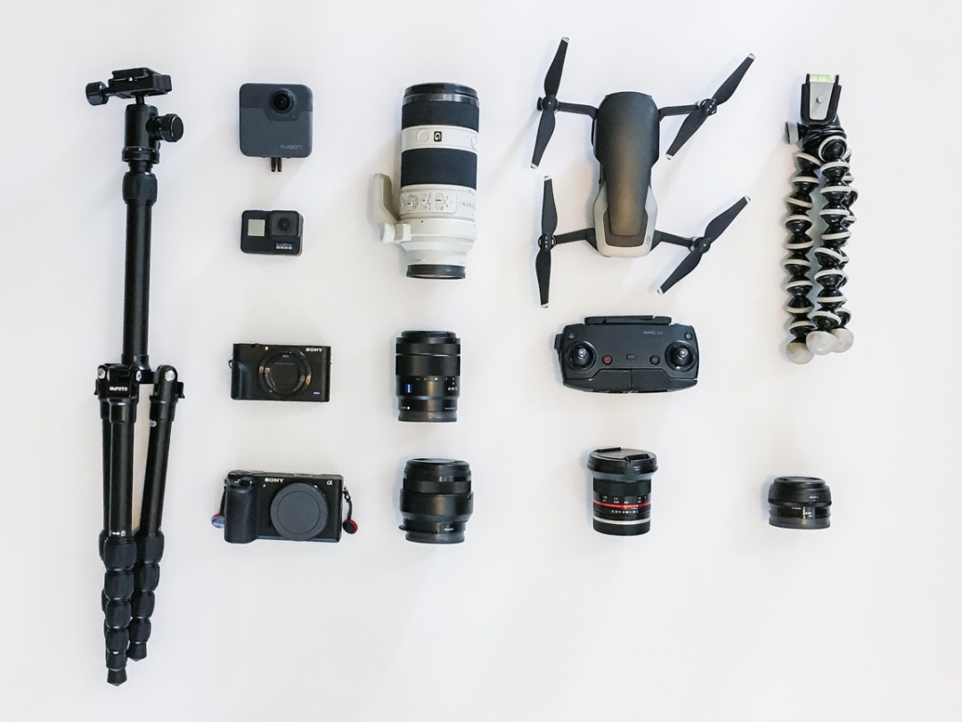 Layflatpicture with camera, lenses, and tripods on a white background