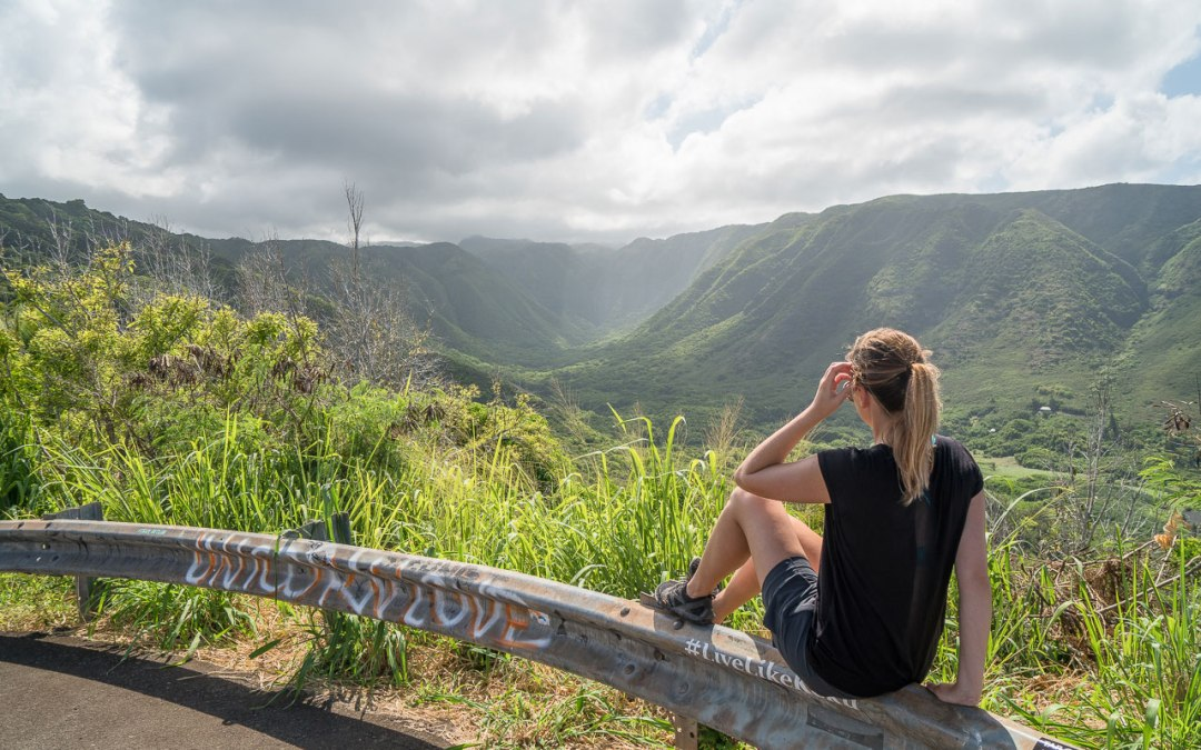 Woman sitting on guardrail looking into Halawa Valley