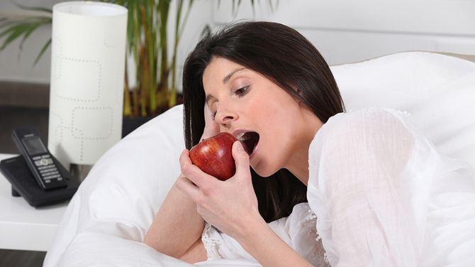 Девушка в постели ест красное яблоко