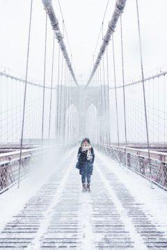 Woman crossing a bridge, snow blowing everywhere