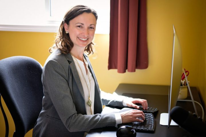 Editor and writer Lori Straus sitting at her computer in her office