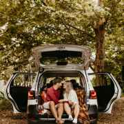 Couple sitting in the trunk of an SUV