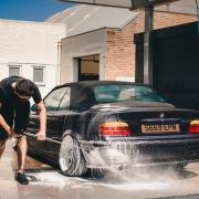 man washing car with car wash products