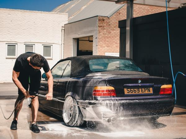 man washing car with car wash products
