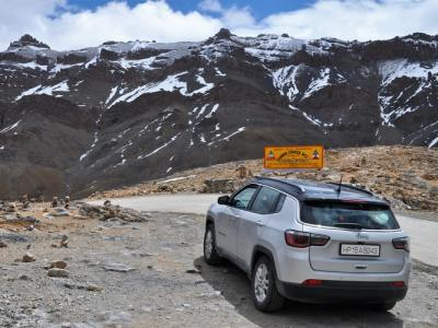 White Jeep Compass in front of snow-peaked mountain range