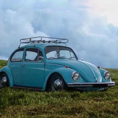 retro powder blue volkswagen beetle in field