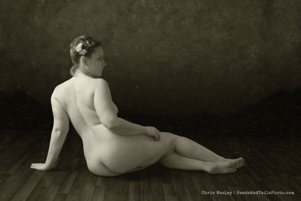 A fine art nude study of a woman. Note the flowers in her hair and the wood floor. By Chris Wooley